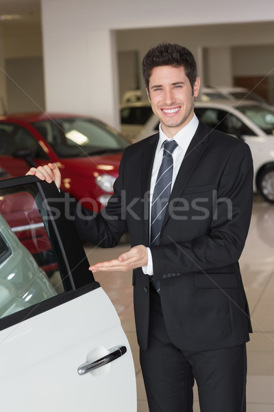 Smiling businessman showing a car for sale Stock photo © wavebreak_media