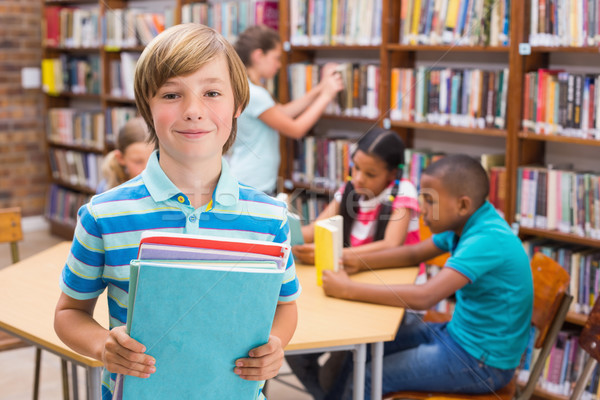Cute pupil smiling at camera in library Stock photo © wavebreak_media
