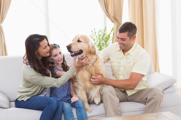 Family stroking dog while sitting on sofa Stock photo © wavebreak_media