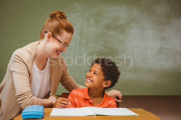 Teacher assisting little boy with homework in classroom Stock photo © wavebreak_media