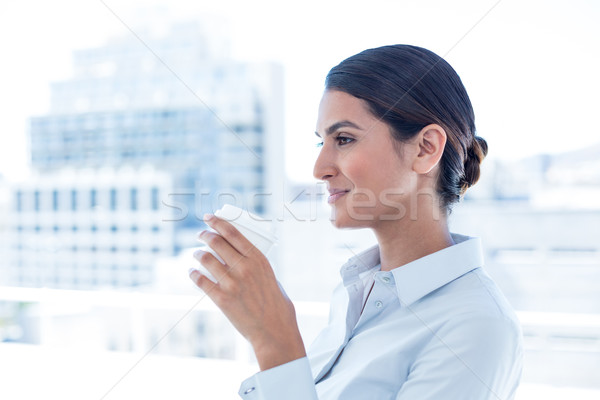 Smiling businesswoman holding disposable cup Stock photo © wavebreak_media