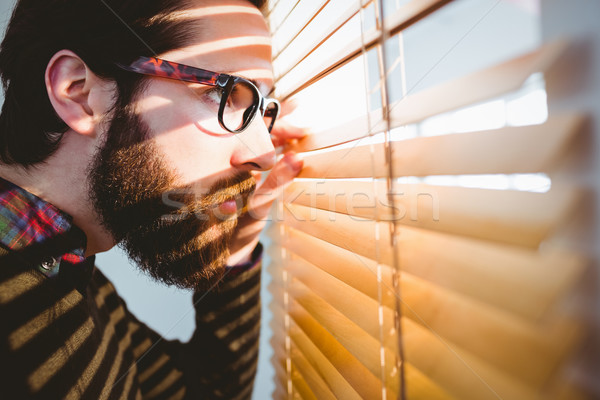 Hipster businessman peeking through blinds Stock photo © wavebreak_media