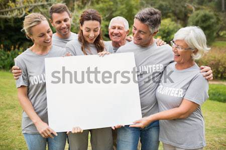 Volunteers with large blank card against green background Stock photo © wavebreak_media
