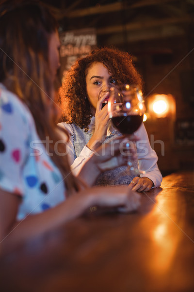 Stock photo: Two young women having red wine in pub