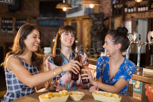 Happy female friends holding toasting beer bottles Stock photo © wavebreak_media