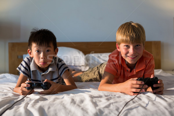 Siblings playing video game on bed Stock photo © wavebreak_media