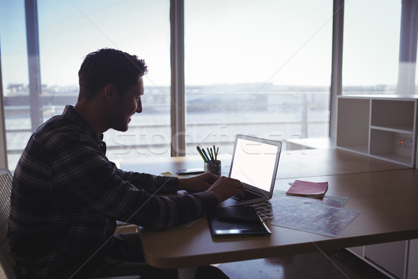 Young businessman using laptop on desk in office Stock photo © wavebreak_media