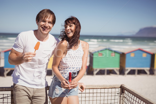 Happy couple eating ice cream standing by railing at beach Stock photo © wavebreak_media