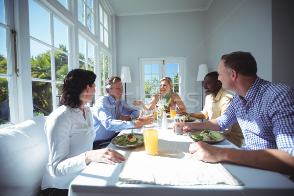 Group of friends interacting while having meal Stock photo © wavebreak_media
