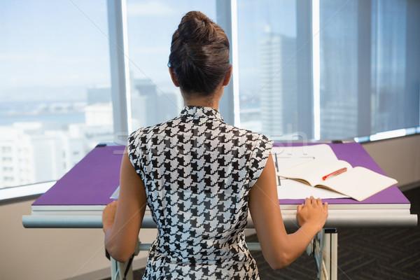 Female architect working on blueprint in office Stock photo © wavebreak_media