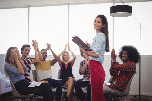 Stock photo: Colleagues applauding for businesswoman in creative office