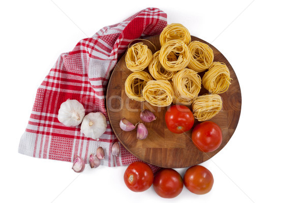 Raw fettuccine with tomatoes, garlic, onions and napkin cloth Stock photo © wavebreak_media