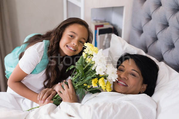 Portrait of smiling grandmother and granddaughter with flower bouquet on bed at home Stock photo © wavebreak_media
