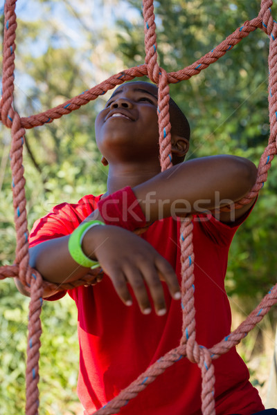 Happy boy leaning on net during obstacle course Stock photo © wavebreak_media