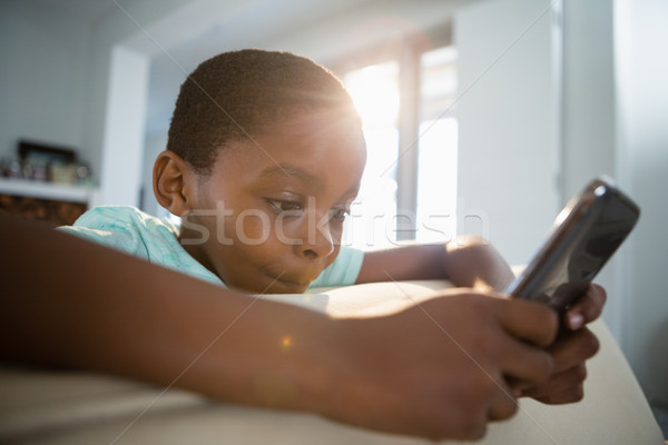 Boy using mobile phone in the living room Stock photo © wavebreak_media
