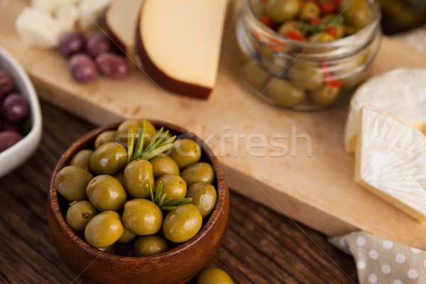 Green olives in container by cheese and vegetable Stock photo © wavebreak_media