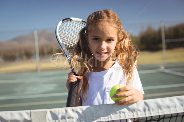 Portrait of girl holding tennis racket and ball Stock photo © wavebreak_media