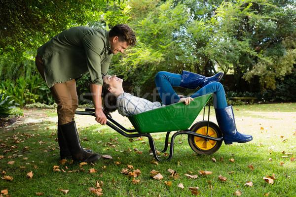 Man interacting with woman while pushing wheelbarrow in garden Stock photo © wavebreak_media