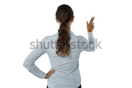 Female executive pretending to touch an invisible screen against white background Stock photo © wavebreak_media