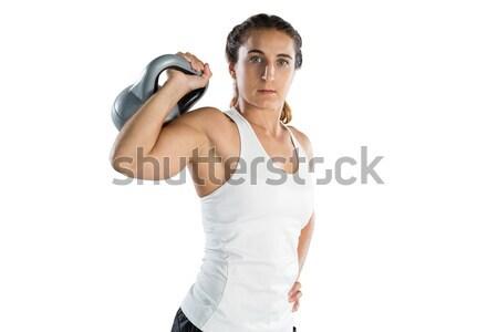 Portrait of female athlete holding kettlebell Stock photo © wavebreak_media