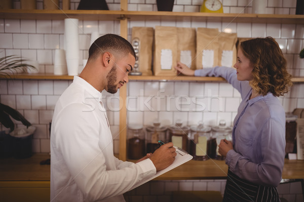 Male owner writing on clipboard while waitress arranging products Stock photo © wavebreak_media