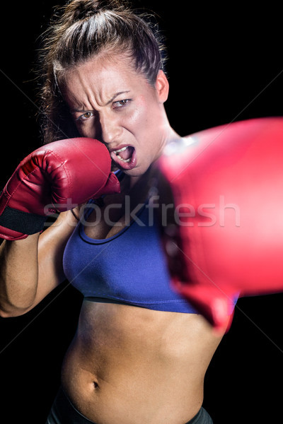 Portrait of aggressive female boxer with fighting stance Stock photo © wavebreak_media