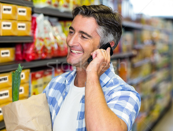 Smiling man on a phone call with grocery bag Stock photo © wavebreak_media
