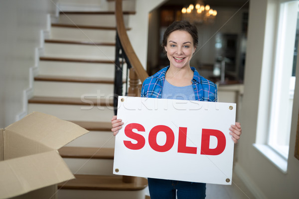 Woman standing in the living room holding sold sign  Stock photo © wavebreak_media