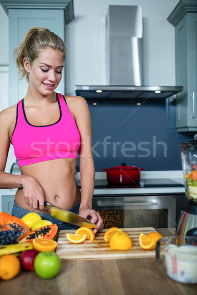 Stock photo: Fit woman cutting fruits