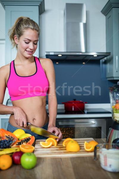 Fitt nő vág gyümölcsök konyha boldog Stock fotó © wavebreak_media