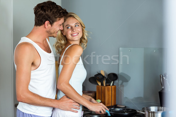 Loving man embracing woman while cooking food in kitchen Stock photo © wavebreak_media