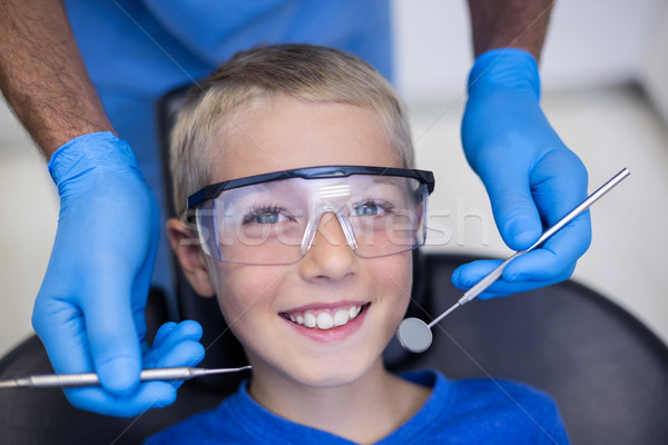 Dentist examining a young patient with tools Stock photo © wavebreak_media