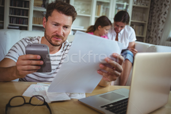 Worried man calculating bills while his wife and daughter sitting on sofa Stock photo © wavebreak_media