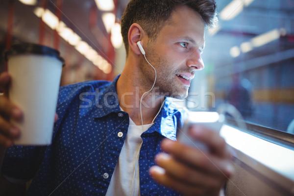 Jóképű férfi hallgat zene mobiltelefon kávé vonat Stock fotó © wavebreak_media