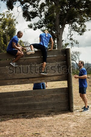 Female trainer assisting fit man to climb over wooden wall during obstacle course Stock photo © wavebreak_media