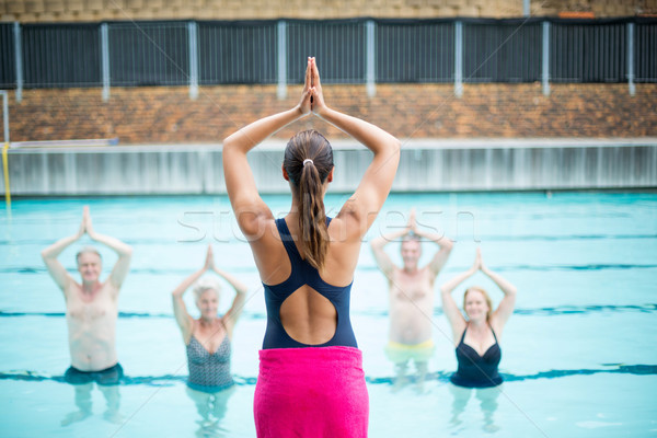 Yoga instructor assisting senior swimmers at poolside Stock photo © wavebreak_media