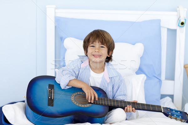 счастливым мало мальчика играет гитаре кровать Сток-фото © wavebreak_media