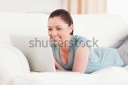 Jolly woman shopping on-line lying on a sofa  Stock photo © wavebreak_media