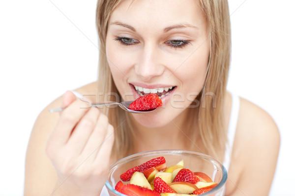 Belle femme manger salade de fruits blanche alimentaire heureux Photo stock © wavebreak_media