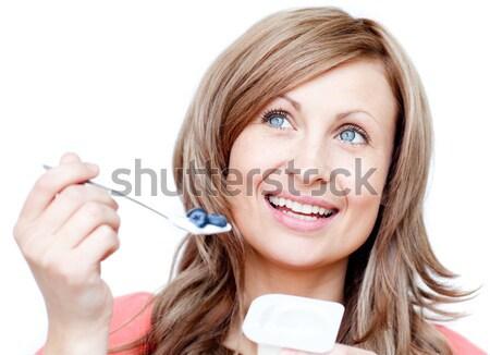 Smiling woman eating a yogurt  Stock photo © wavebreak_media