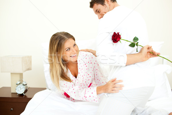 Attentive man giving a rose to his wife in the bedroom Stock photo © wavebreak_media