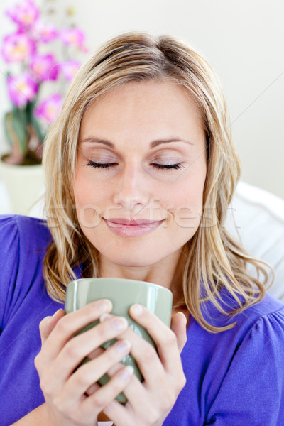 Attractive young woman enjoying her coffee with closed eyes at home Stock photo © wavebreak_media