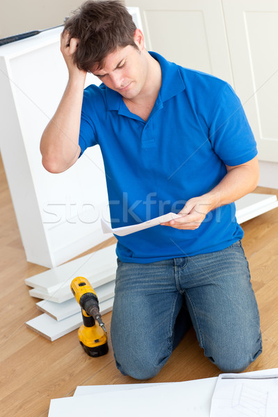 Incomprehensive young man reading the instructions to assemble furniture in the kitchen Stock photo © wavebreak_media