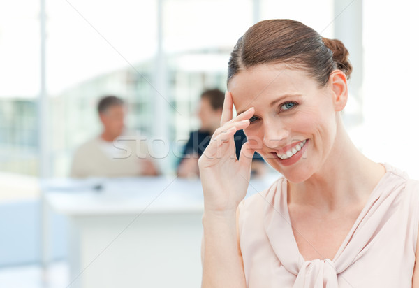 Smiling businesswoman looking at the camera while her coworkers are talking in the office Stock photo © wavebreak_media