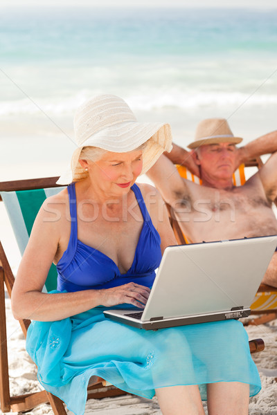 Femme travail portable mari dormir plage Photo stock © wavebreak_media