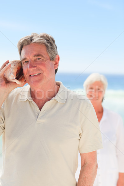 Man listening his shell with his wife behind him Stock photo © wavebreak_media