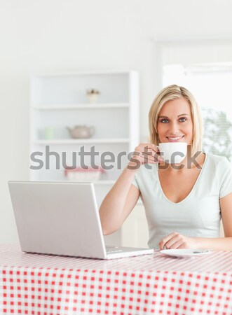 Good looking woman posing while eating a bowl of pasta in her kitchen Stock photo © wavebreak_media