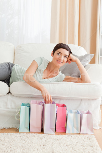 Stock photo: Young woman with shopping bags in her living room