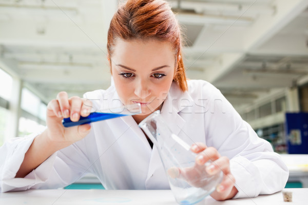 Beautiful scientist pouring liquid in a laboratory Stock photo © wavebreak_media