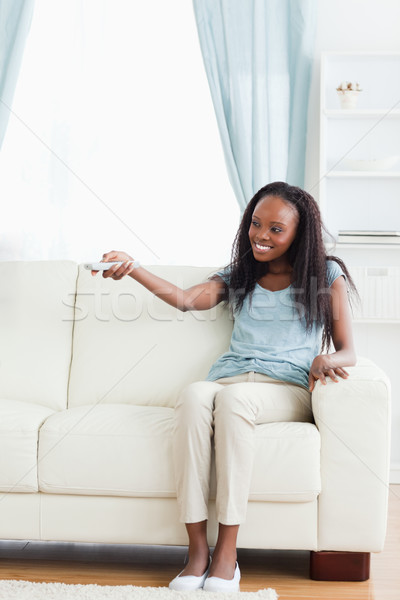 Smiling woman in living room with remote Stock photo © wavebreak_media